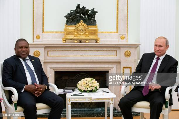 Russian President Vladimir Putin and Mozambique's President Filipe Nyusi pose for pictures prior to their meeting at the Kremlin in Moscow on August...