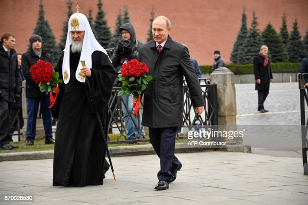 Russian President Vladimir Putin and Patriarch of Russia Kirill arrive to lay flowers at the monument of Minin and Pozharsky on the Red Square near...