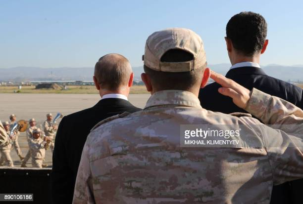 TOPSHOT Russian President Vladimir Putin and President of Syria Bashar alAssad inspect a military parade during their visit to the Russian air base...