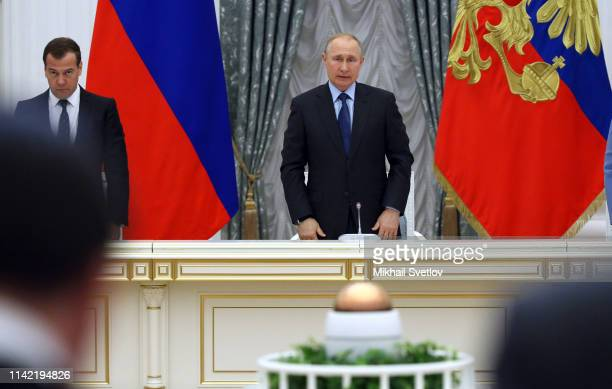 Russian President Vladimir Putin and Prime Minister Dmitry Medvedev stand during the moment of silence commemorating the victims of the Aeroflot...