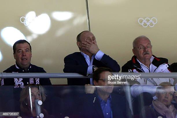 Russian President Vladimir Putin and Prime Minister Dmitry Medvedev watch the Men's Ice Hockey Preliminary Round Group A game between Russia and...