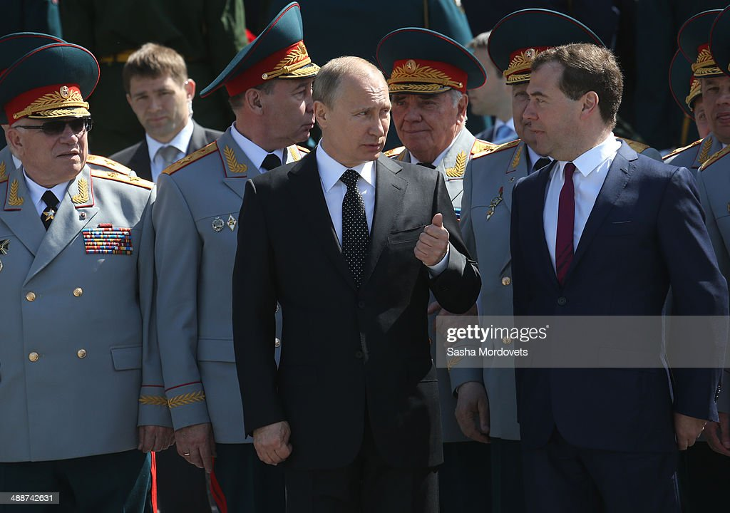 Russian President Vladimir Putin and Prime Minister Dmitry Medvedev (R) attend a wreath laying ceremony at the Unknown soldier tomb near the Kremlin on May 8, 2014 in Moscow, Russia. Russia celebrates the Victory Day and the end of the WWII war on May 9.