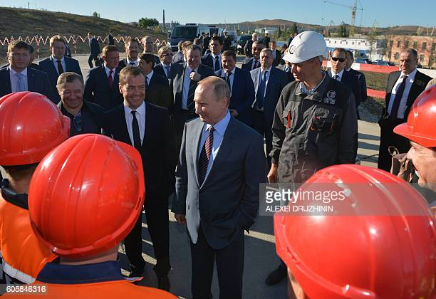 Russian President Vladimir Putin and Prime Minister Dmitry Medvedev meet with workers as they visit the site of the underconstruction bridge across...