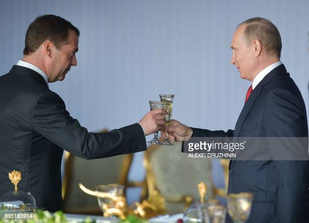 """Russian President Vladimir Putin and Prime Minister Dmitry Medvedev make a toast during a holiday reception marking """"Russia Day"""" in Moscow on June..."""