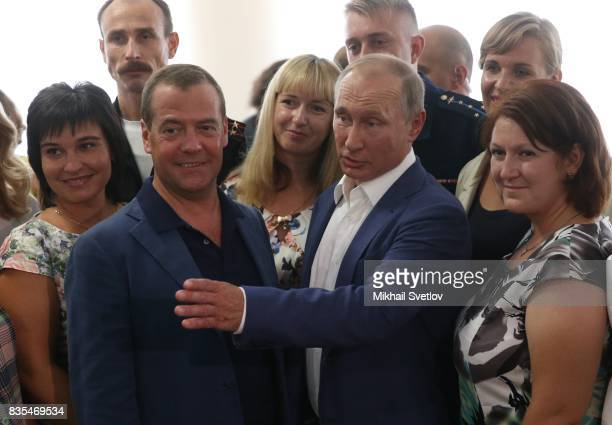 Russian President Vladimir Putin and Prime Minister Dmitry Mevedev pose for a group photo while visiting a newly opened school on August 18 2017 on...