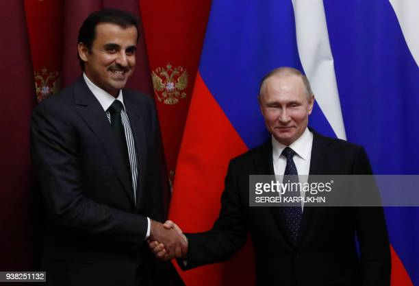 Russian President Vladimir Putin and Qatar's Emir Sheikh Tamim bin Hamad alThani shake hands during a signing ceremony following a meeting at the...