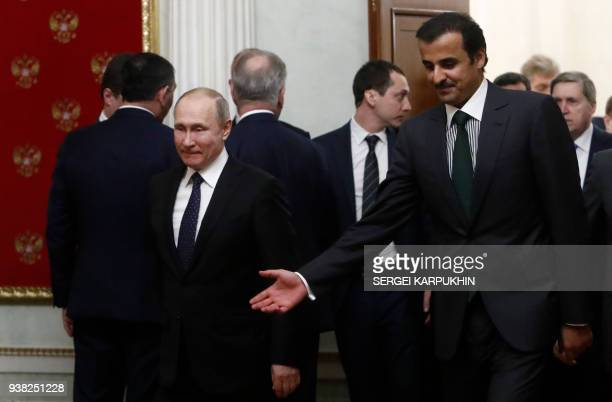 Russian President Vladimir Putin and Qatar's Emir Sheikh Tamim bin Hamad alThani enter a hall for a signing ceremony following a meeting at the...
