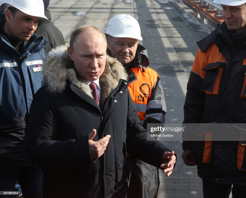 Russian President Vladimir Putin (L) and Russian billionaire and businessman Arkady Rotenberg visit the construction site for the Crimean bridge which is being built to connect the Krasnodar region of Russia and Crimean Peninsula across the Kerch Strait on March 14, 2018 on the Taman Peninsula, on the border with Russia and the annexed Ukrainian territory of Crimea.