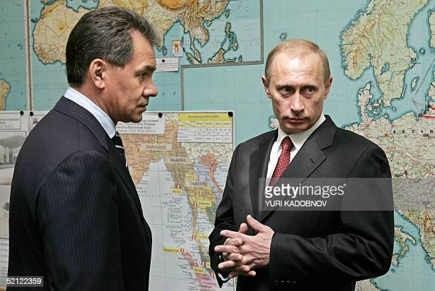 Russian President Vladimir Putin and Russian Emergency Minister Sergey Shoygu stand in front of the world map during the Emergency Ministry session...