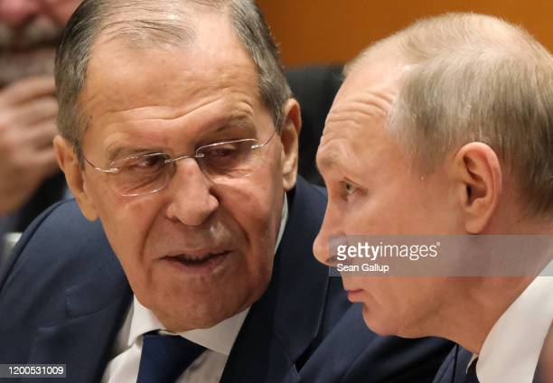 Russian President Vladimir Putin and Russian Foreign Minister Sergey Lavrov attend the main session at an international summit on securing peace in...