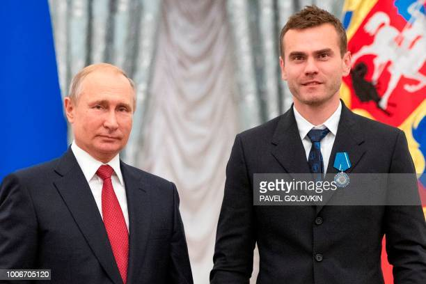 Russian President Vladimir Putin and Russia's national football team goalkeeper Igor Akinfeev pose for pictures during an awards ceremony for the...