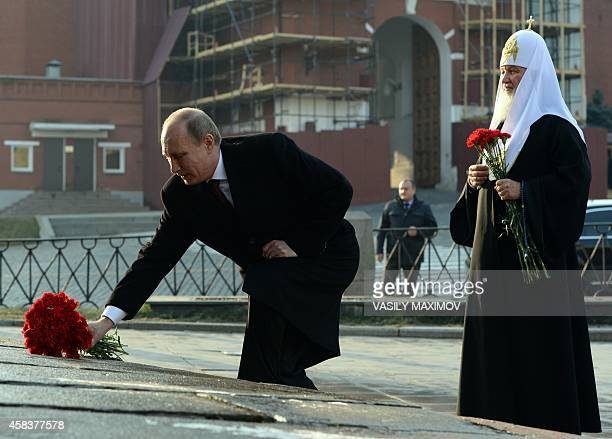 Russian President Vladimir Putin and Russia's Patriarch Kirill lay flowers on November 4 2014 during a ceremony on Red square in Moscow during the...