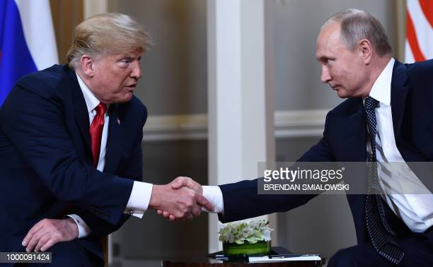 Russian President Vladimir Putin and US President Donald Trump shake hands before a meeting in Helsinki, on July 16, 2018.