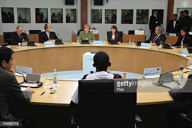 Russian President Vladimir Putin and US President George W Bush listen to German Chancellor Angela Merkel during a meeting during the first day of...