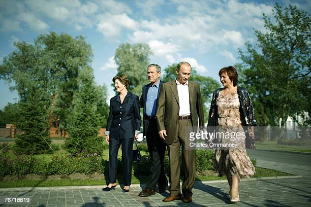 'EXCLUSIVE' Russian President Vladimir Putin and US President George W Bush wave as they pose with their wives Laura Bush and Lyudmila Putina during...