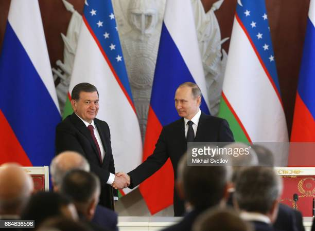 Russian President Vladimir Putin and Uzbek President Shavkat Mirziyoyev shake hands at the signing ceremony at the Grand Kremlin Palace on April 5,...