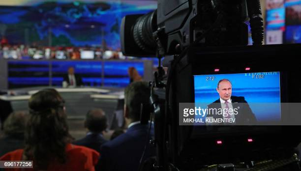 """Russian President Vladimir Putin answers questions at the Gostiny Dvor studio during the annual """"Direct Line with Vladimir Putin broadcast live"""" by..."""