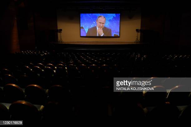 Russian President Vladimir Putin appears on a screen in a hall at the World Trade Centre's congress centre as he addresses his annual press...