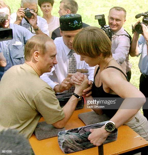 Russian President Vladimir Putin arm wrestles a woman while taking part in midsummer festivities June 25 2000 in Kazan Tatarstan