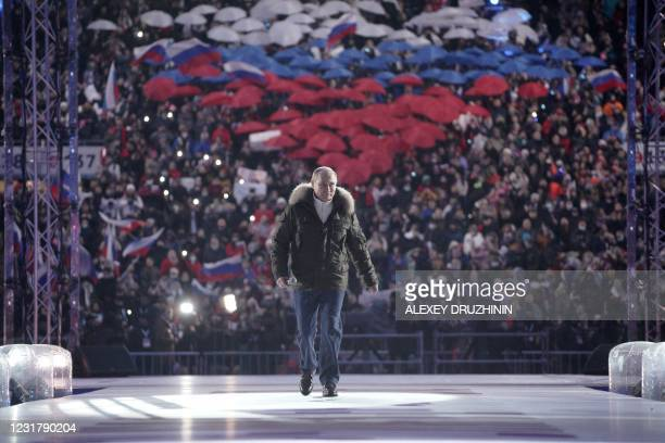 Russian President Vladimir Putin attends a concert marking the seventh anniversary of Russia's annexation of Crimea at the Luzhniki stadium in Moscow...
