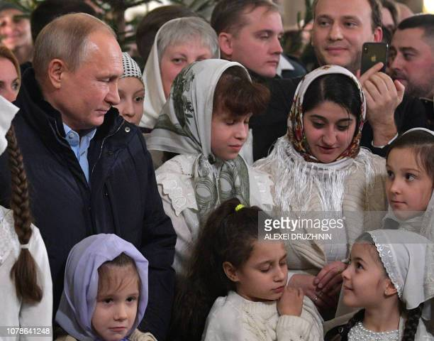 Russian President Vladimir Putin attends a midnight mass at the Cathedral of the Transfiguration of the Savior of All the Guards in St Petersburg on...