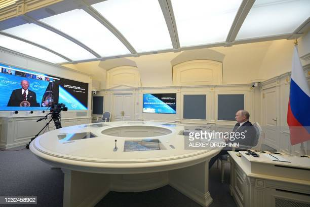 Russian President Vladimir Putin attends a video conference meeting as US President Joe Biden is seen on screen, as part of the virtual US-hosted...