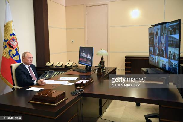 Russian President Vladimir Putin attends a videoconference meeting on the opening of multifunctional medical centres in several Russian regions,...
