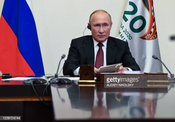 Russian President Vladimir Putin attends the G20 summit hosted by Saudi Arabia via video conference at the Novo-Ogaryovo state residence, outside...