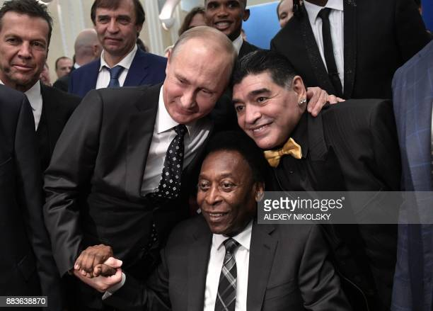 TOPSHOT Russian President Vladimir Putin Brazilian football legend Pele and Argentina's former midfielder Diego Maradona pose for pictures ahead of...