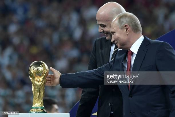 Russian President Vladimir Putin caresses the trophy next to FIFA president Gianni Infantino during the trophy ceremony at the end of the Russia 2018...