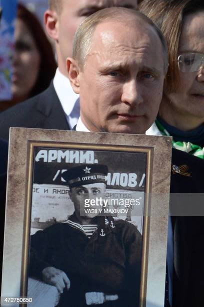Russian President Vladimir Putin carries a portrait of his father as he takes part in the Immortal Regiment march during the Victory Day celebrations...