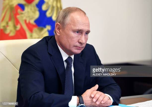 Russian President Vladimir Putin chairs a meeting with members of the government via a teleconference call at the Novo-Ogaryovo state residence...