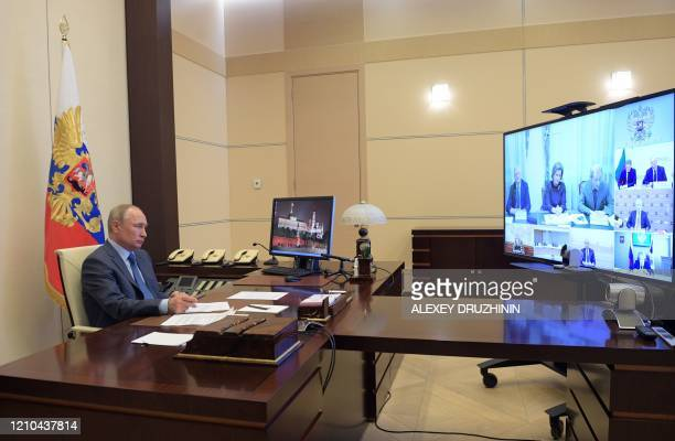 TOPSHOT Russian President Vladimir Putin chairs a video conference meeting on the COVID19 coronavirus situation at the NovoOgaryovo state residence...