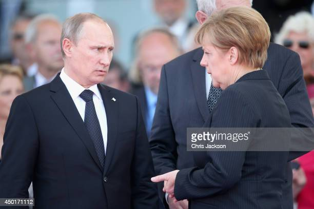 Russian President Vladimir Putin chats to German Chancellor Angela Merkel as they attend a Ceremony to Commemorate DDay 70 on Sword Beach on June 6...