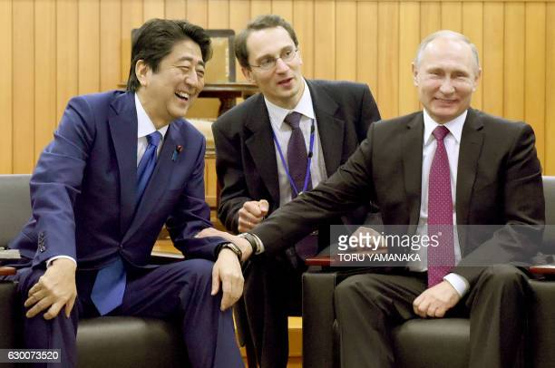 Russian President Vladimir Putin chats with Japanese Prime Minister Shinzo Abe during a visit to the Kodokan judo hall in Tokyo on December 16 2016...