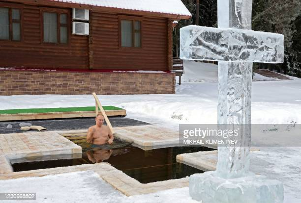 Russian President Vladimir Putin crosses himself as he plunges into the icy waters during the celebration of the Epiphany holiday in Moscow region on...