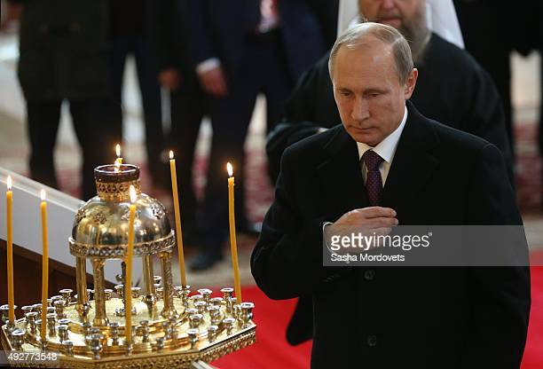 Russian President Vladimir Putin crosses himself while visiting the Dormition Cathedral of Russian Orthodox Church on October 15 2015 in Astana...