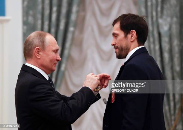 Russian President Vladimir Putin decorates Russian ice hockey player and gold medalist of the 2018 Pyeongchang Winter Olympic Games Pavel Datsyuk...