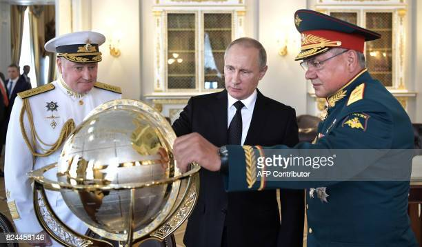 Russian President Vladimir Putin Defence Minister Sergei Shoigu and Commander in Chief of the Russian Navy Vladimir Korolev watch a terrestrial globe...