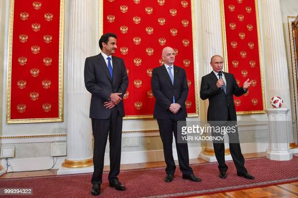 Russian President Vladimir Putin delivers a speech as FIFA President Gianni Infantino and Emir of Qatar Sheikh Tamim bin Hamad AlThani looks on...