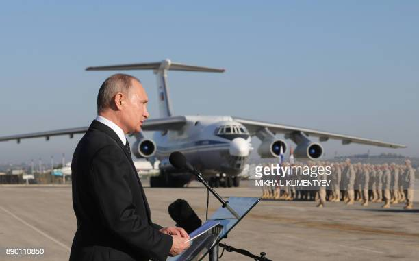 Russian President Vladimir Putin delivers a speech as he inspects a parade during his visit to the Russian air base in Hmeimim in the northwestern...