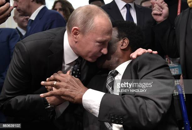 TOPSHOT Russian President Vladimir Putin embraces Brazilian football legend Pele ahead of the Final Draw for the 2018 FIFA World Cup football...