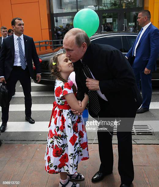 Russian President Vladimir Putin embrasses a girl while visiting the Dmitry Rogachev Center for Paediatric Haematology Oncology Immunology on June 1...