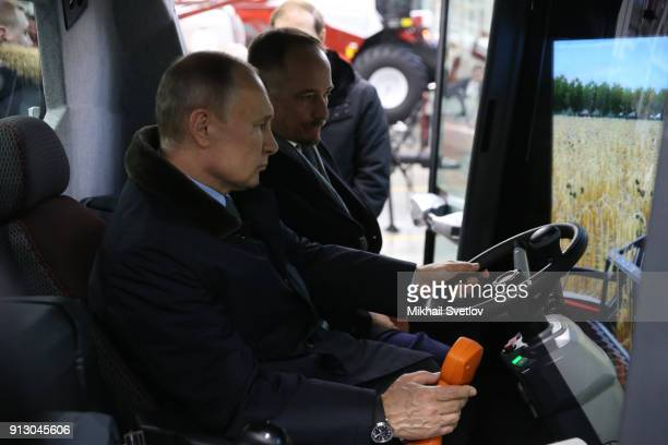 Russian President Vladimir Putin examines a tractor simulator while visiting a tractor plant of Rostselmash on February 1, 2018 in Rostov-on-Don,...