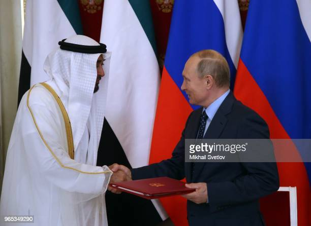 Russian President Vladimir Putin exchange documents with Abu Dhabi's Crown Prince and Deputy Supreme Commander of UAE's Armed Forces Sheikh Mohammed...