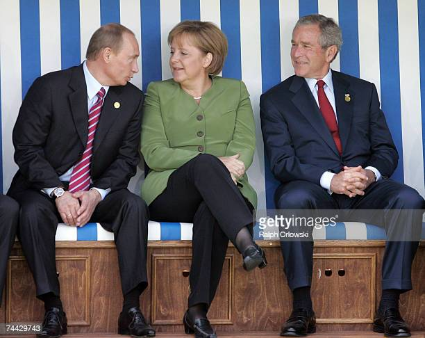 Russian President Vladimir Putin, German Chancellor Angela Merkel and U.S. President George W. Bush chat as they sit in a beach chair during the...