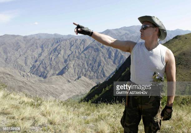 Russian President Vladimir Putin gestures as he takes a break near the foothills of the Western Sayan Mountains in the Republic of Tuva, 15 August...