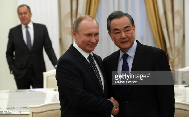 Russian President Vladimir Putin greets Chinese Foreign Minister Wang Yi as Russian Foreign Minister Sergey Lavrov looks during their talks at the...
