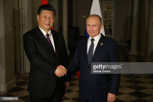 Russian President Vladimir Putin greets Chinese President Xi Jinping during their meeting at the BRICS Summit in Johannesburg South Africa July2018...