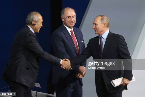 Russian President Vladimir Putin greets Egyptian billionaire and businessman Nassef Sawiris as CEO of London Stock Exchange Group Xavier Rolet looks...